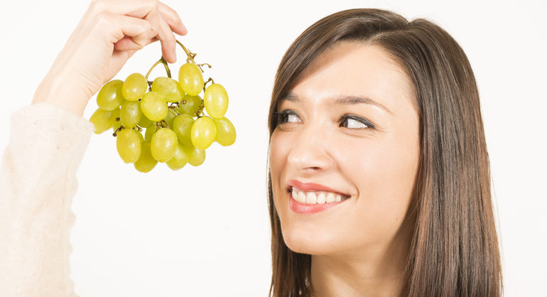 Young woman holding up a bunch of green grapes, smiling.
