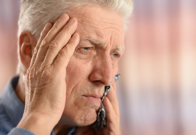 Elderly man with his hand on his head, holding his tooth in pain